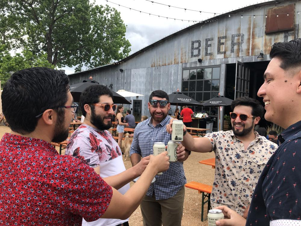 Photo of five young men toasting cans of beer on a Twisted Texas Tour, they are on a patio in front of metal building with sign reading Beer