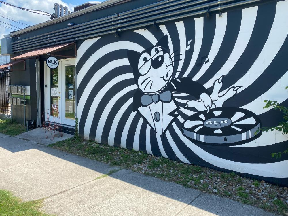 Photo of the exterior of BLK Vinyl  with a black and white mural of a cat in a tuxedo in the center of a spiral design, spinning a record with one finger
