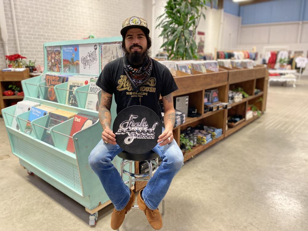 Man sitting on stool inside of Feels So Good Records Record Shop in Austin Texas