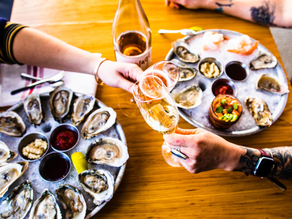 Two people clink wine glasses over trays of oysters at Parkside in Austin Texas