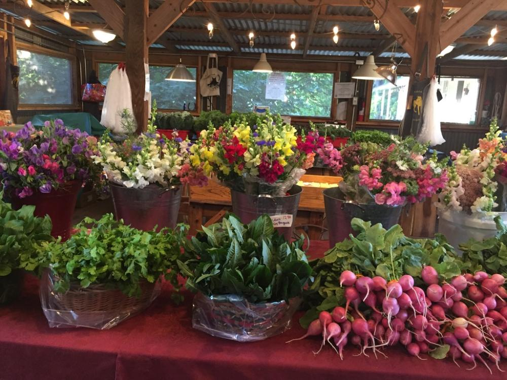 Boggy Creek Farm stand with baskets of greens, radishes and buckets of flowers