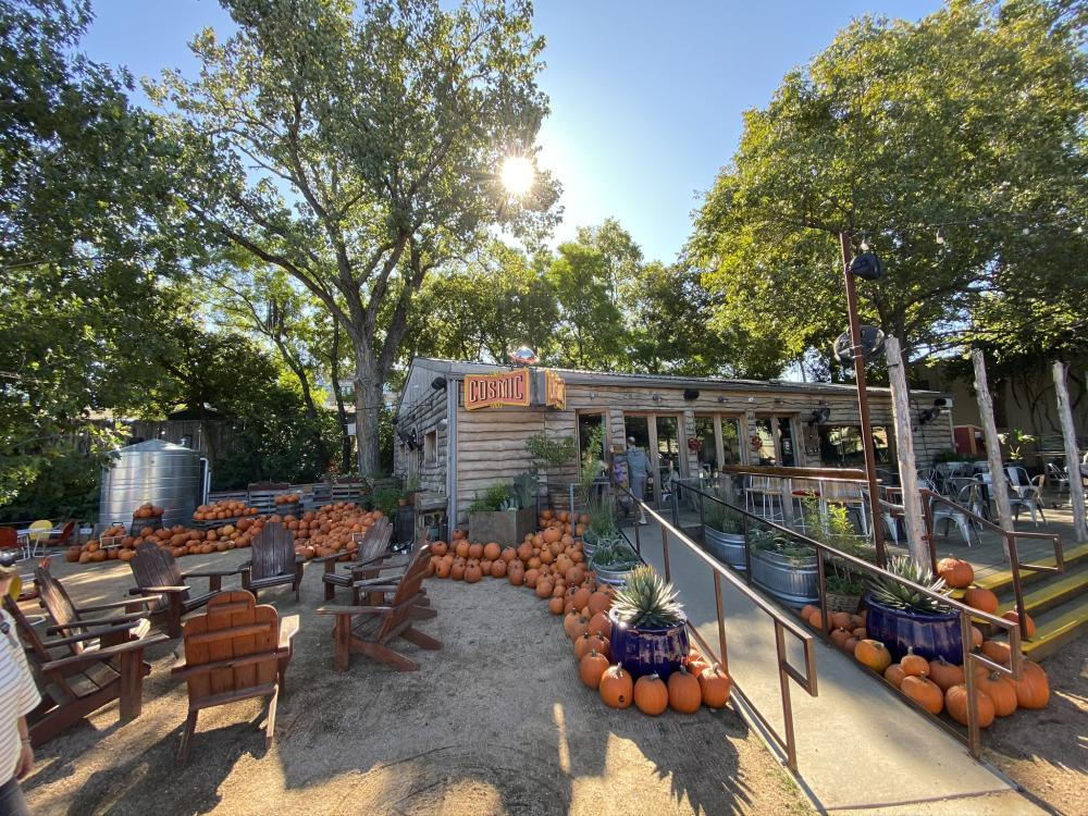 Exterior and patio at Cosmic Coffee and Beer decorated for fall with tons of pumpkins