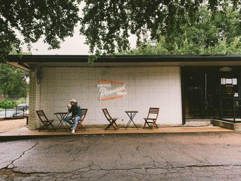 Woman drinking coffee on patio at Pinewood Coffee and Beer in Waco Texas