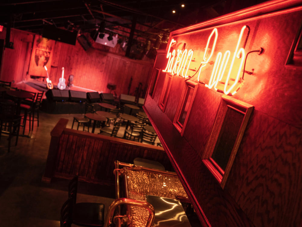 """Red neon sign reading """"Saxon Pub"""" above a indoor bar. In the background, two guitars are visible sitting on a stage"""