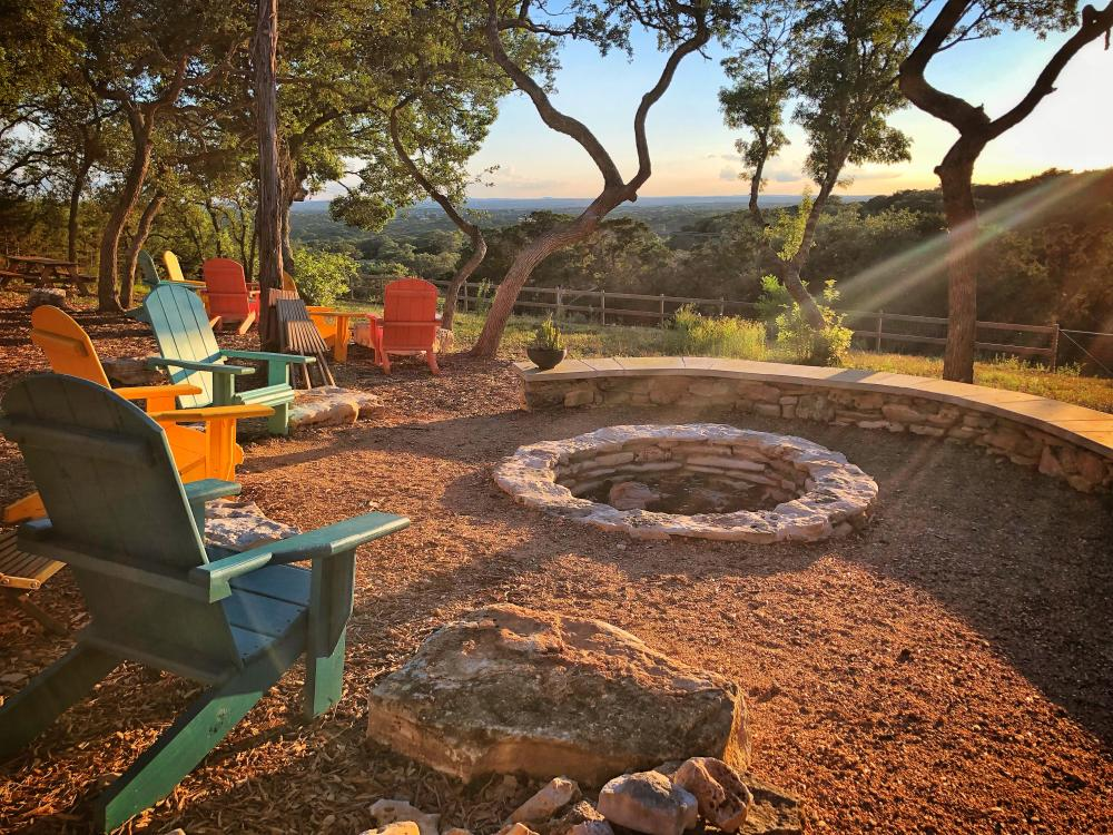 Adirondack chairs surrounding fire pit at The Shady Llama in Wimberley Texas