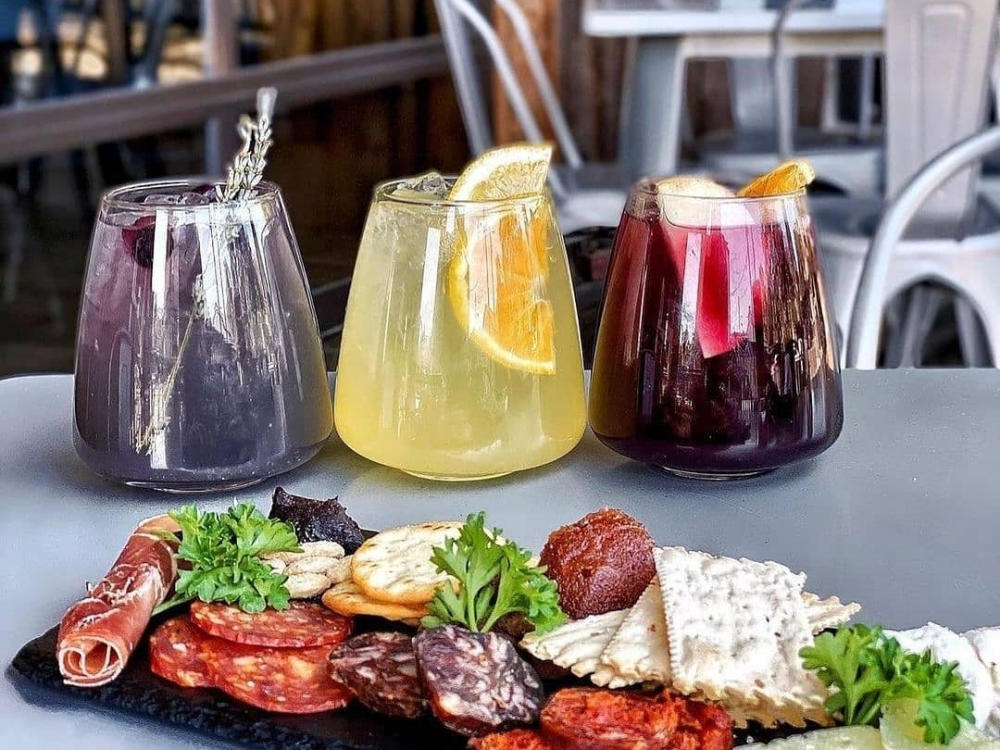 photo of three colorful cocktails sitting on a table behind a plate of assorted cheeses, crackers and cured meats at Botero Tapas + Wine Bar in Boerne Texas