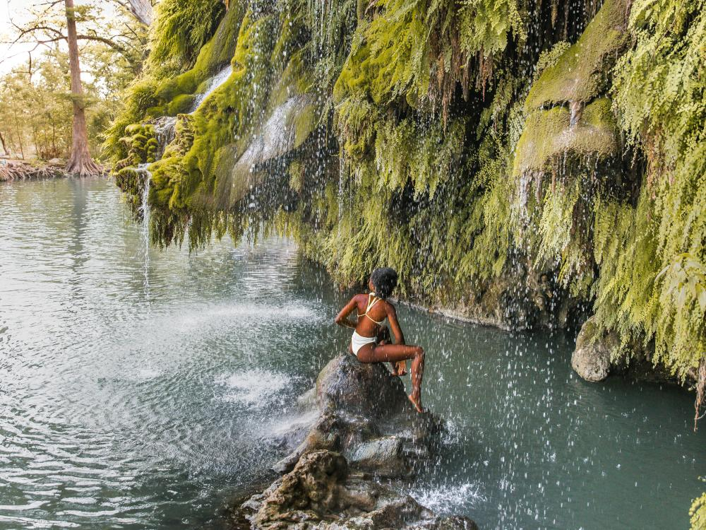 Woman sitting on a rock under waterfall at Krause Springs near Austin Texas