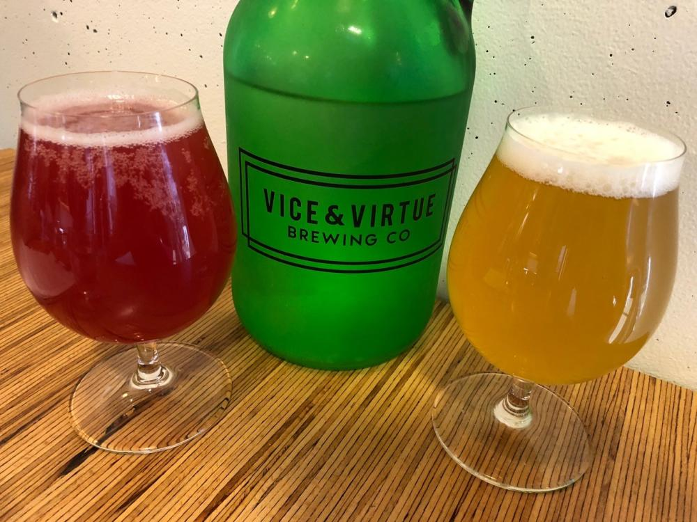 """Two glasses of beer flank a large green bottle with the words """"Vice & Virtue Brewery"""" on a wooden table against a white wall"""
