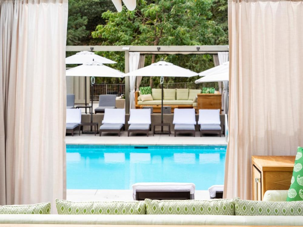 Quiet pool waters lined by lounge chairs at the Meadowood Pool Cabana.