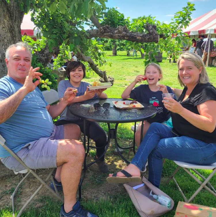 A family enjoying grapes wine and cheese at Terhune Orchards in Mercer County