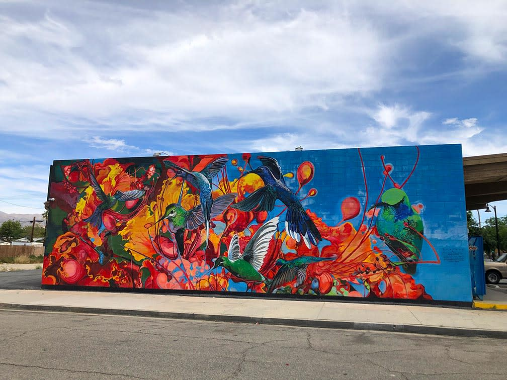 Colorful mural with hummingbirds and paint splatter