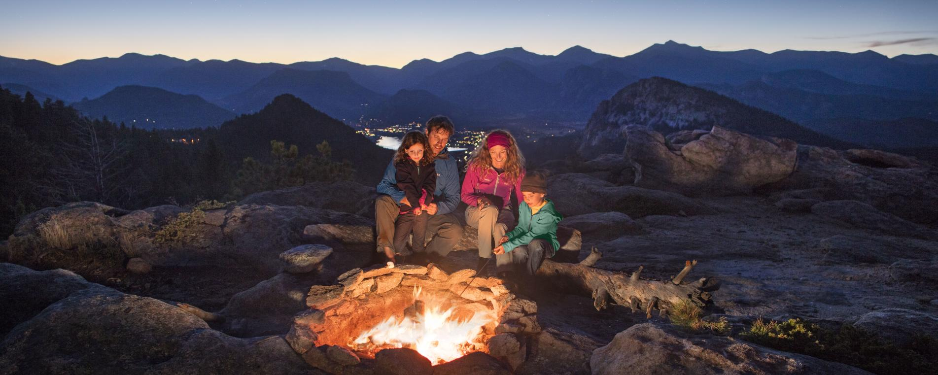 Family around a campfire above Estes Park