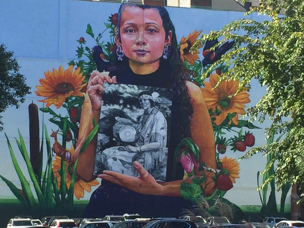 Mural (2018) depicting a member of the Narragansett Indian Tribe holding a photo of Princess Red Wing, a Narragansett/Pokanoket-Wampanoag elder who founded the Tomaquag Museum (Exeter).  Located at 32 Custom House Street.