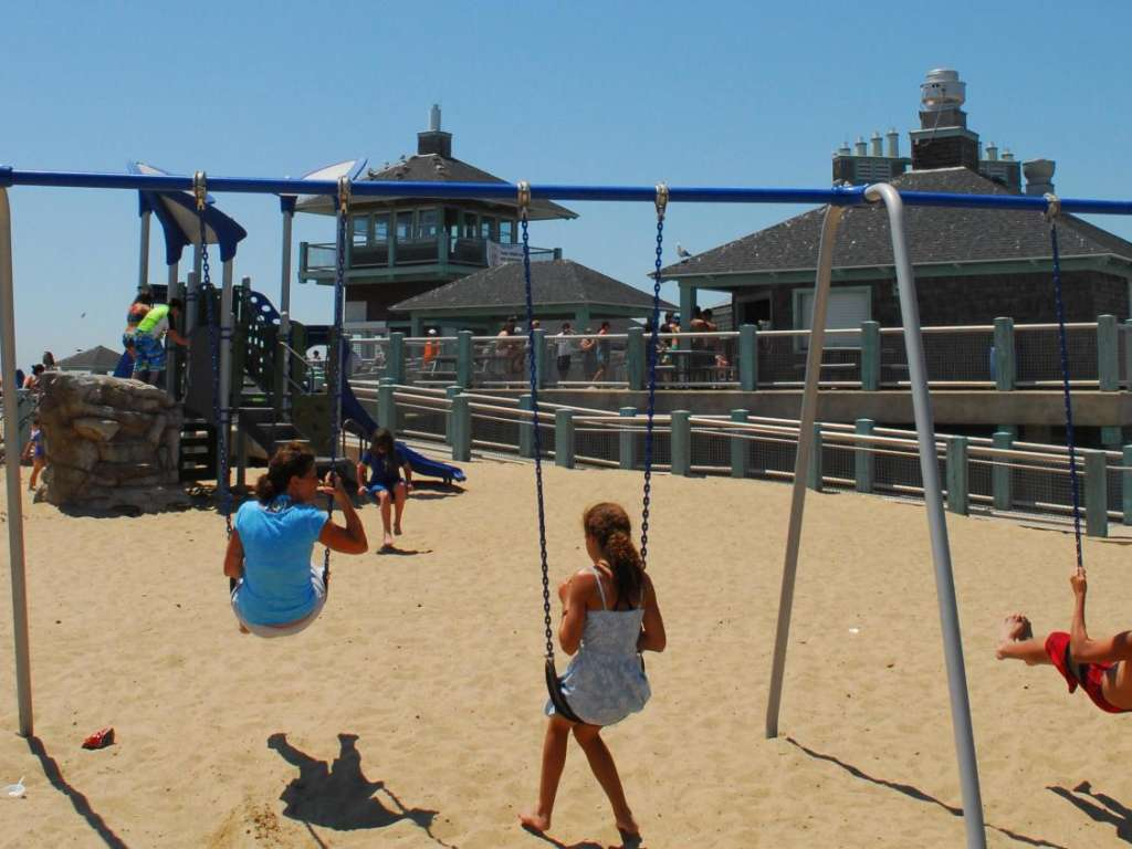 Children on swings facing a slide and climber at Misquamicut Beach