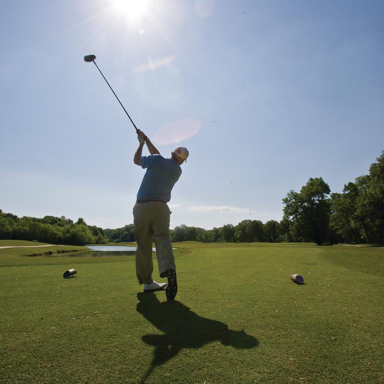 Golf RTJ Huntsville Hampton Cove Golfer Swinging Club Bright Sun.jpg