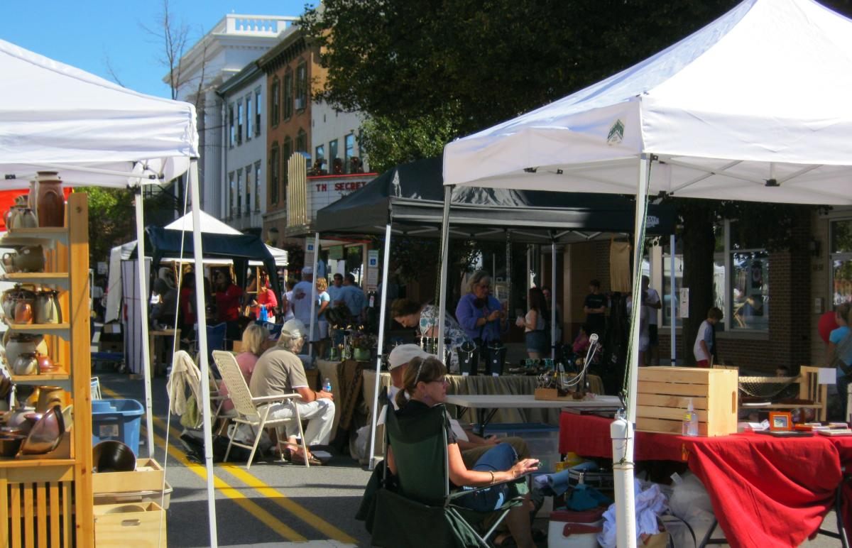 Vendors sitting at their tents at the Harvest of the Arts