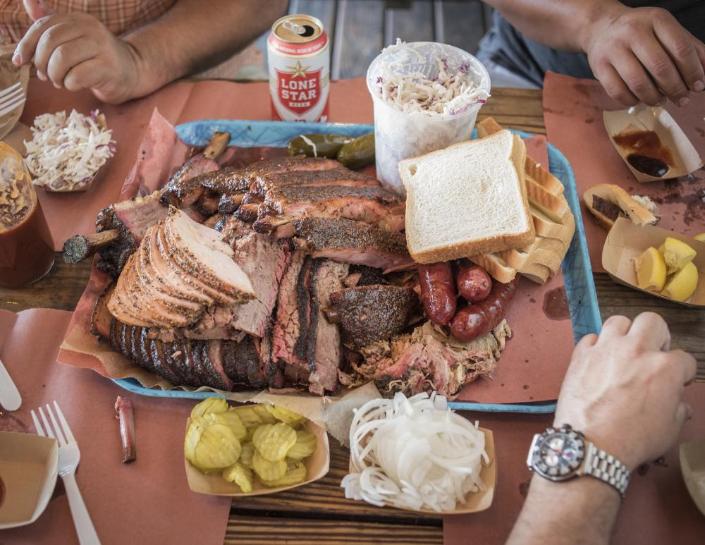 three men sit around a platter of BBQ and sides at Franklin Barbecue in Austin Texas
