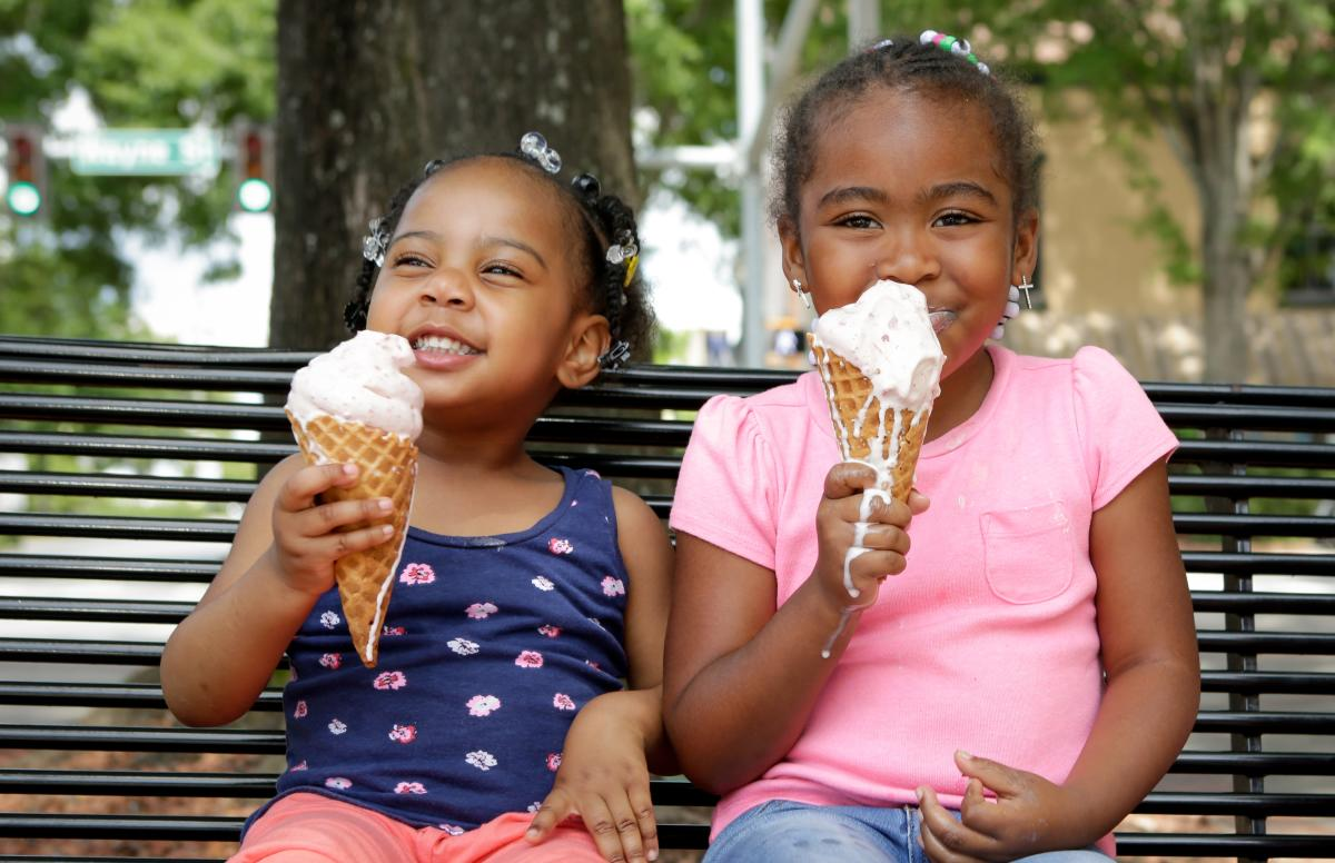 Little girls enjoying ice cream on a park bench