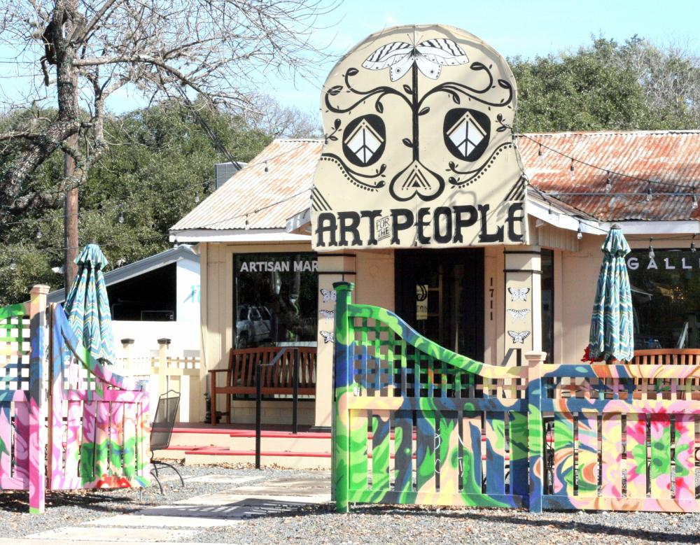 Exterior of Art for the People gallery with sign and painted fence in front of building