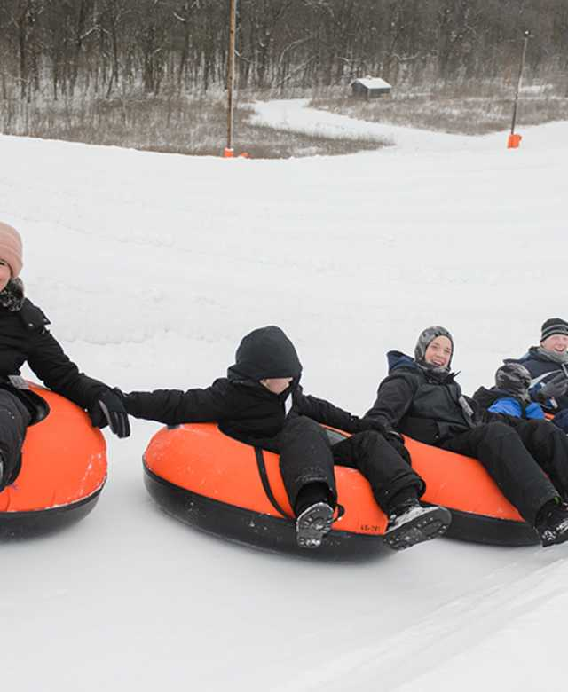 5 people snow tubing down a snowy slope