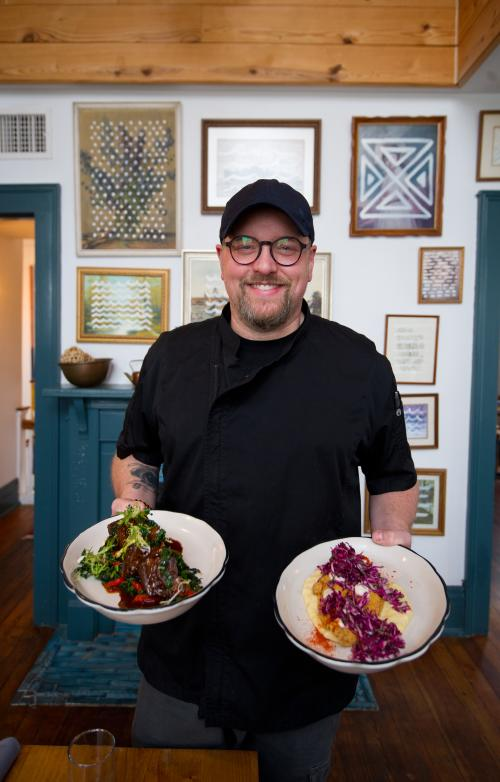 Chef holding plated dishes at Portage House