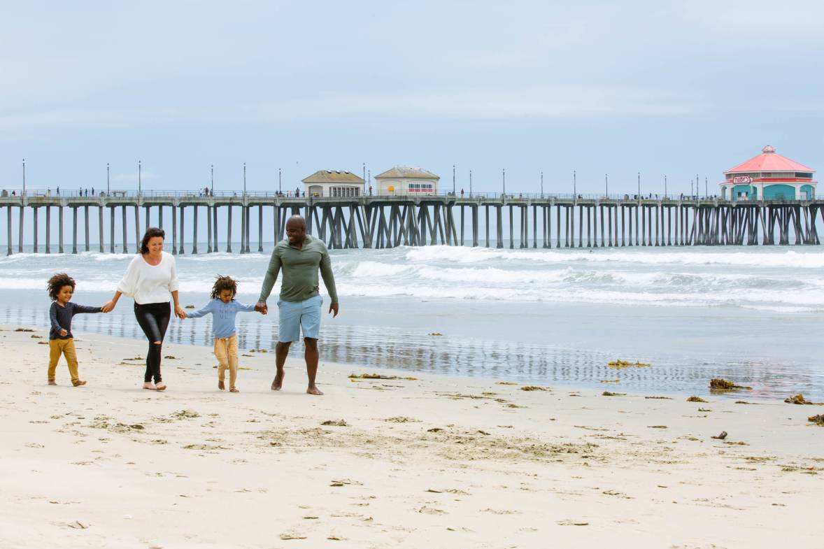 Father's Day in Huntington Beach. Family walking on the sand with the Pier in the background.