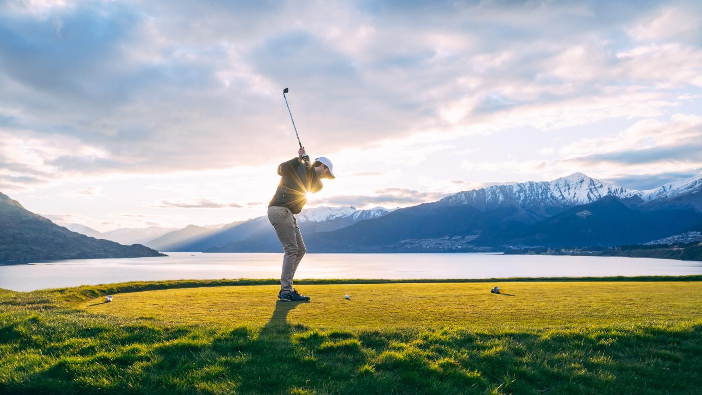Man golfing with lake and mountain views