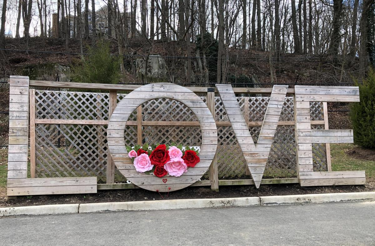 wooden LOVEwork sign in Occoquan decorated with red and pink flowers
