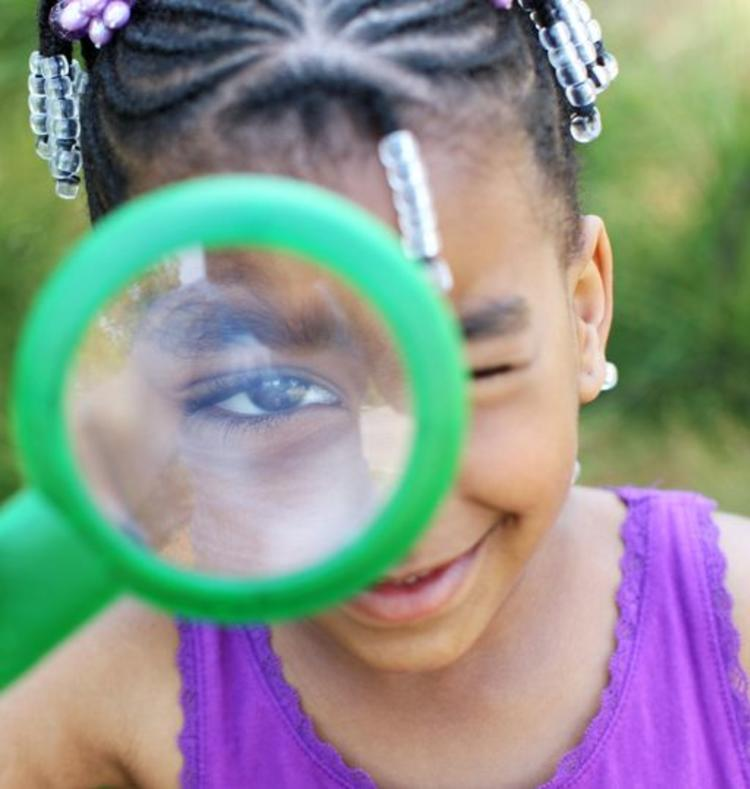 Little girl looking through a magnify glass