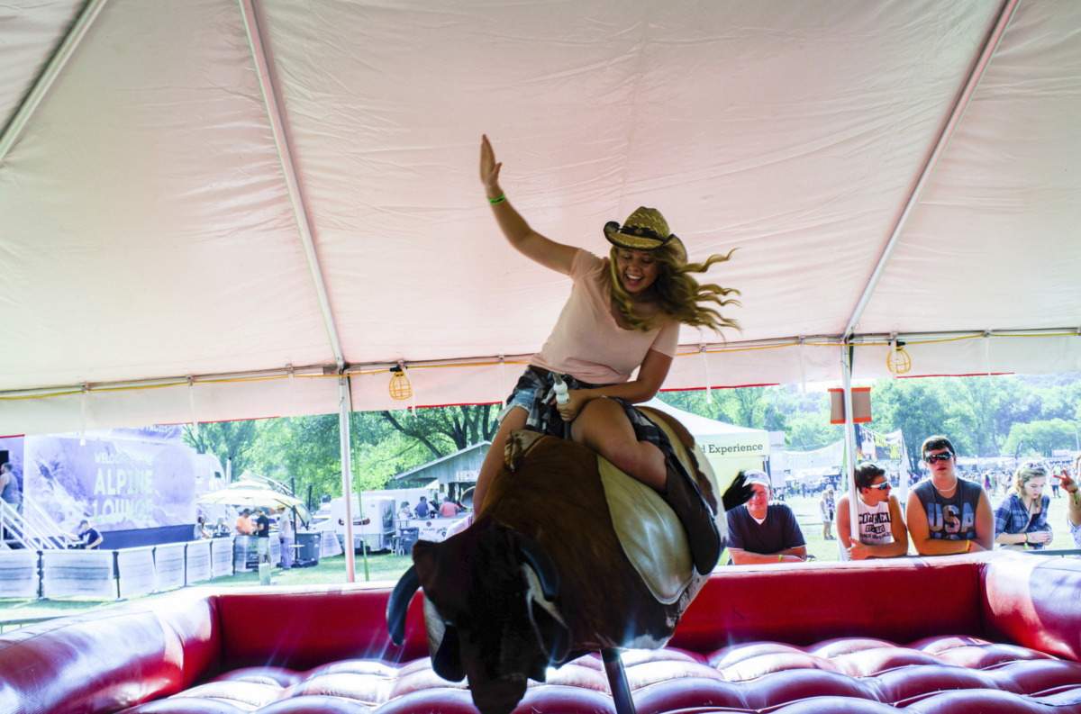 A woman riding a fake bull at Country Jam in Eau Claire, Wisconsin