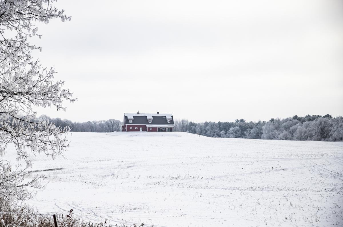 Snow covered field and red house in the distance from Hwy 178