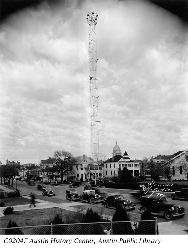 Historic black and white photo of a Moonlight Tower in Austin with 1930s era cars in foreground