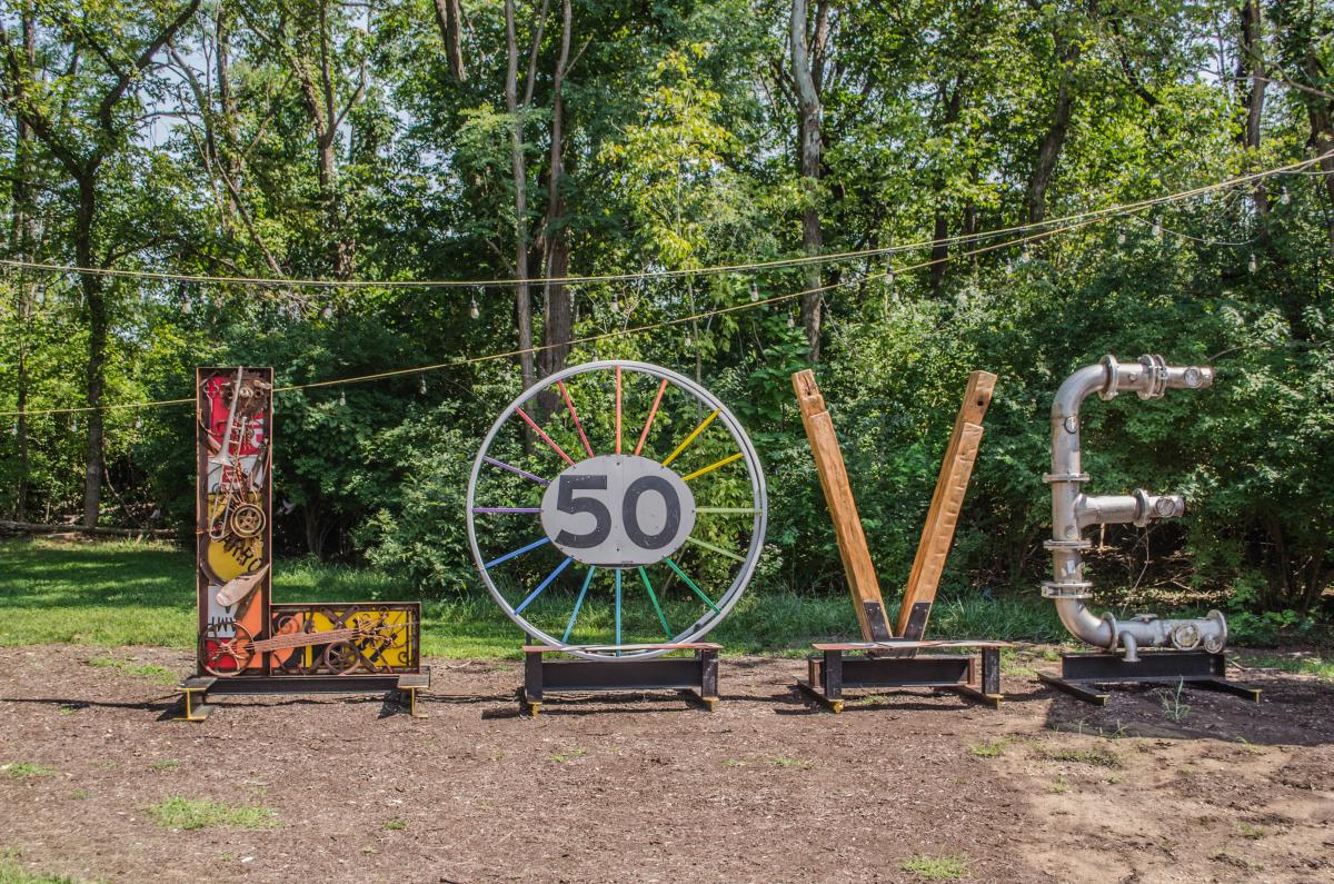 Large letters make up the word 'LOVE' as part of an installation at Black Dog Salvage. The L is made of industrial elements and musical instruments, the O is made of two industrial spools painted in the colors of the rainbow, the V is made of reclaimed pine beams, and the E is made from stainless steel piping.