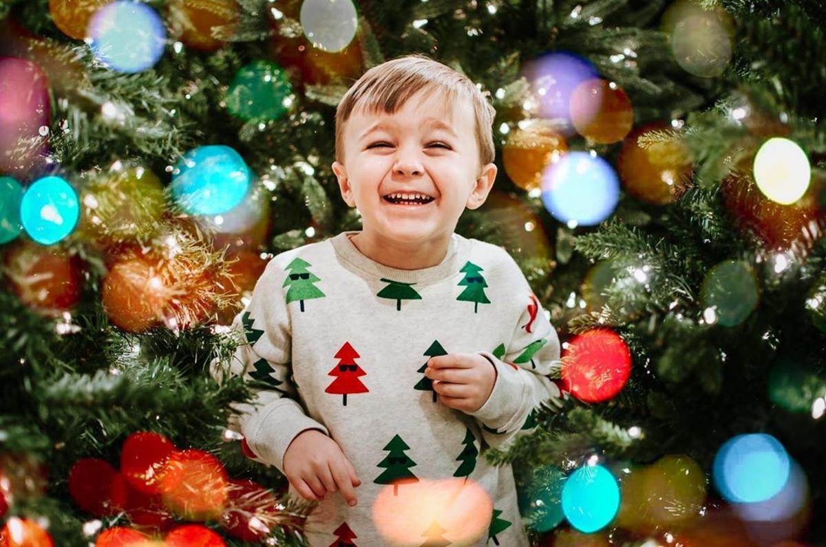 Little boy laughing and smiling, surrounded by Christmas trees and holiday lights, while he enjoys the world's largest Christmas store at Bronner's CHRISTmas Wonderland in Frankenmuth