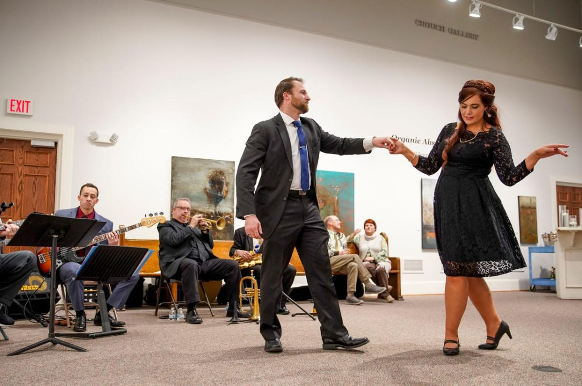 a couple dancing with a band in a museum gallery