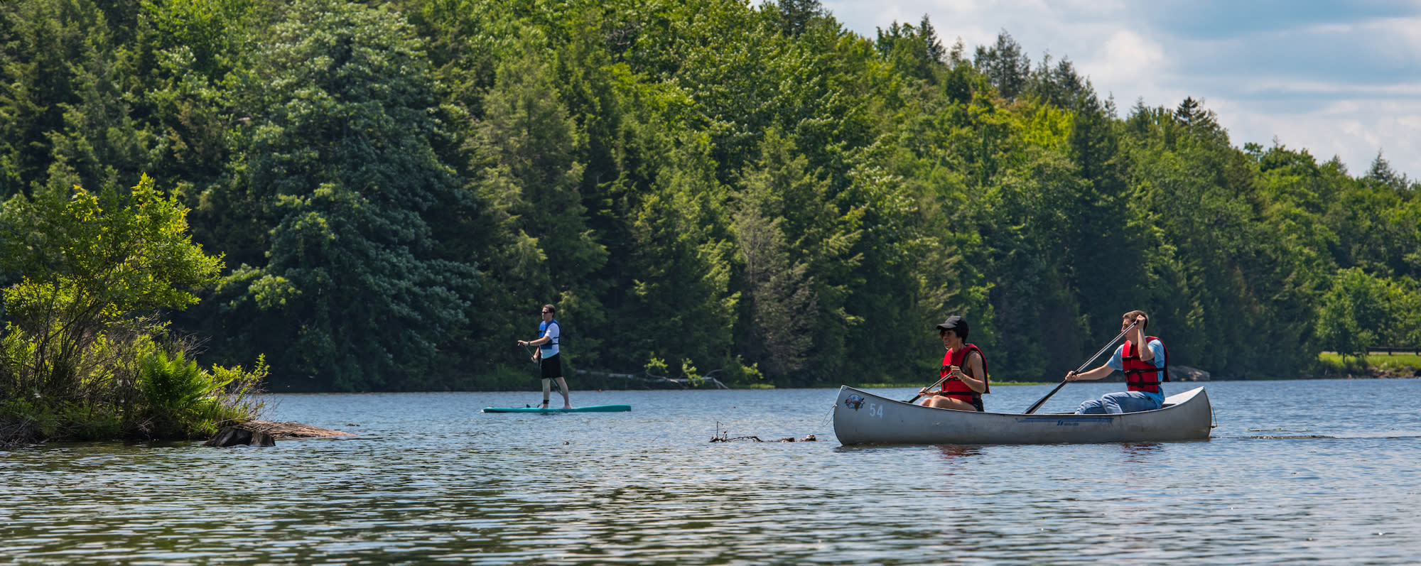A photo of two people in a canoe and one person paddle boarding on a lake on Noth-South Lake Campground