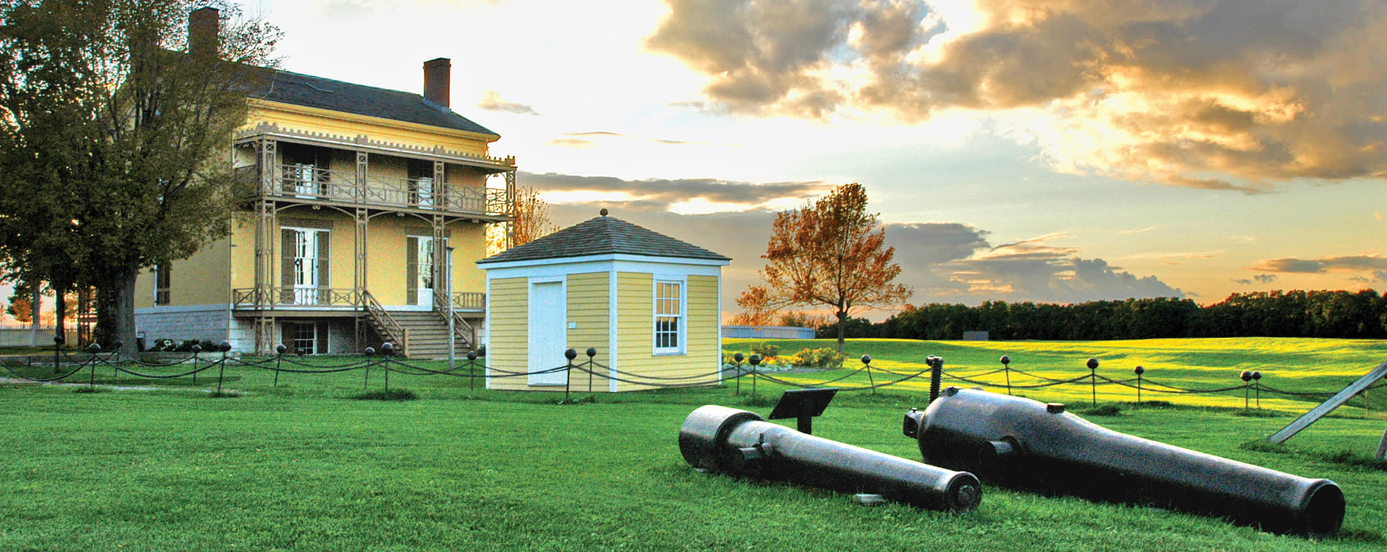 Two cannons resting on the field at Sackets Harbor Historic Site with a house and out-house in the background