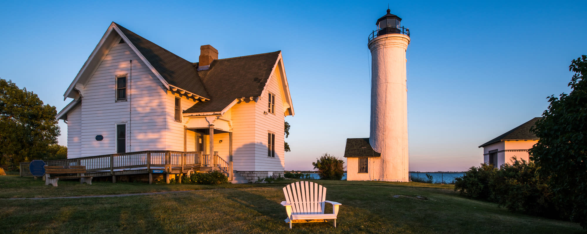 A photo of the exterior of Tibbetts Point Lighthouse with an Adirondack chair on the lawn