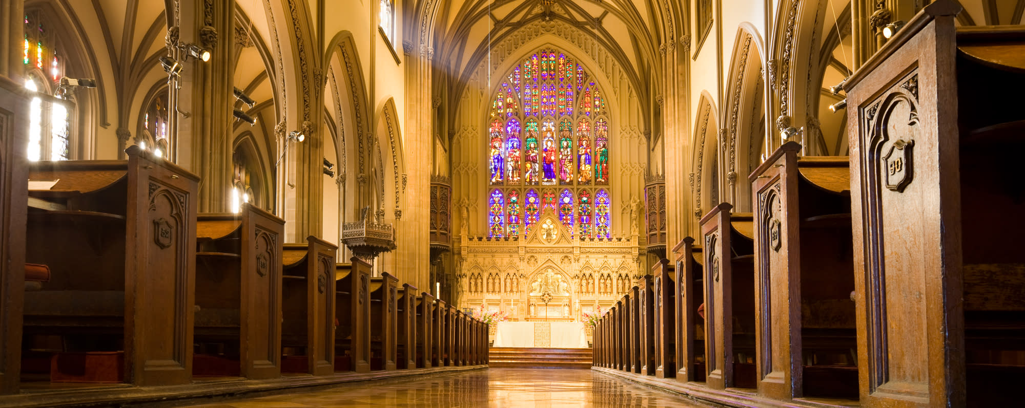 The interior pews and stained glass windows of Trinity Church in New York City