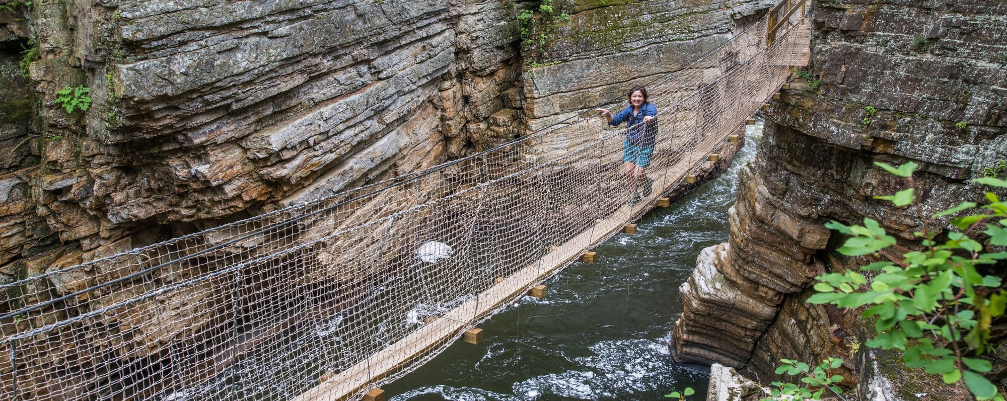 A person walks on a bridge between rocks in Ausable Chasm