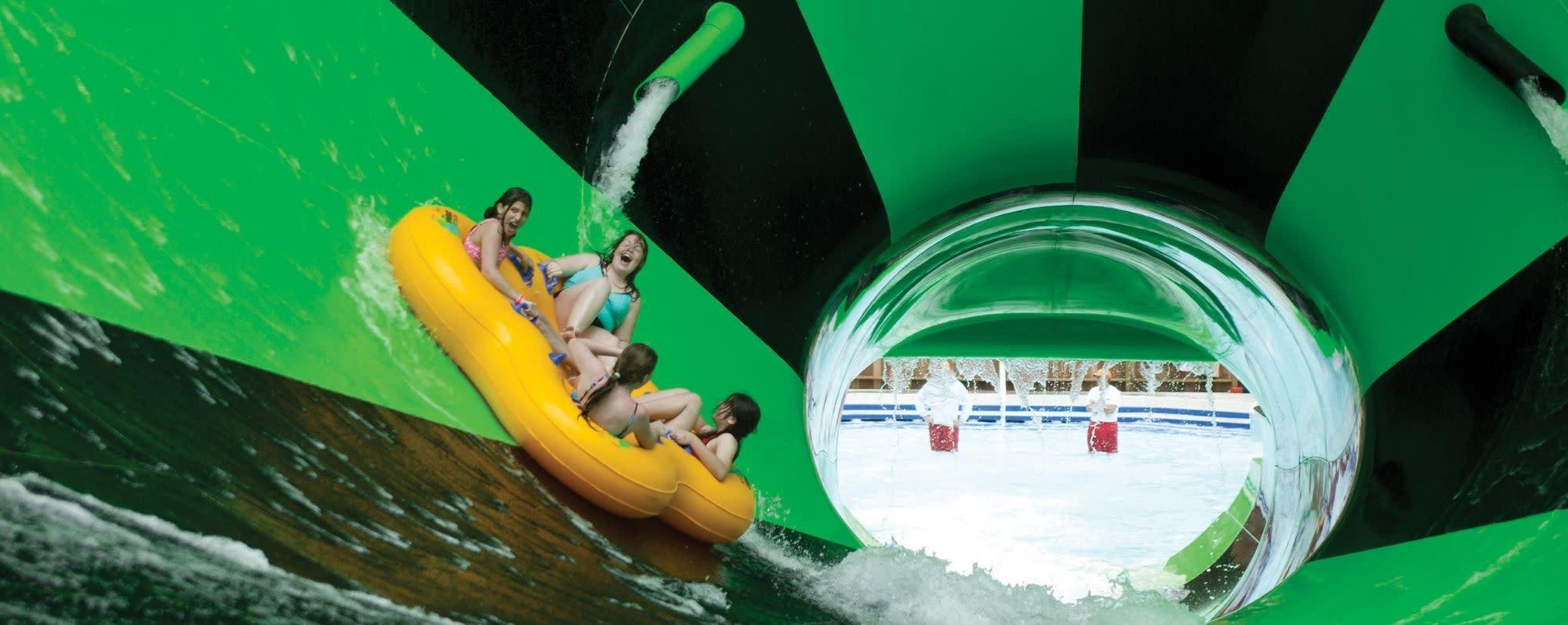 Four people ride the Alien Invasion water slide at Splish Splash Water Park