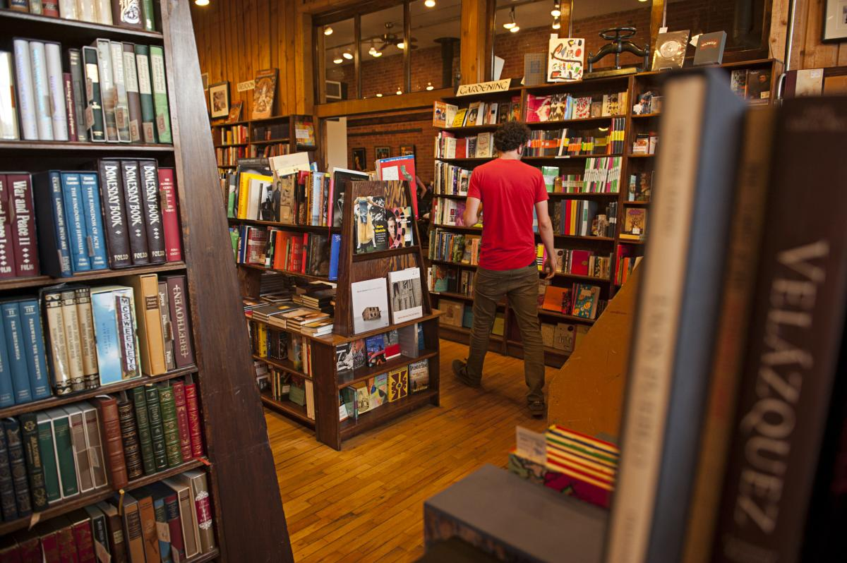 Man browsing bookshelves at the Trident Bookstore in Boulder