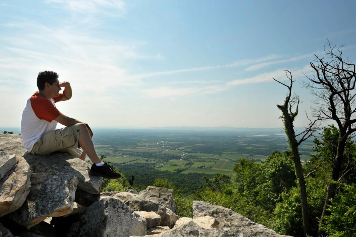 Hiker sitting on a rock and shading his eyes with his hand to overlook the view on Waggoners Gap