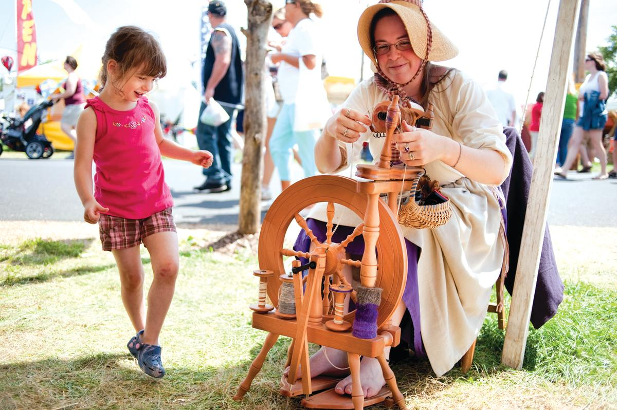 Little girl watching a woman spin yarn at the Kutztown Folk Festival
