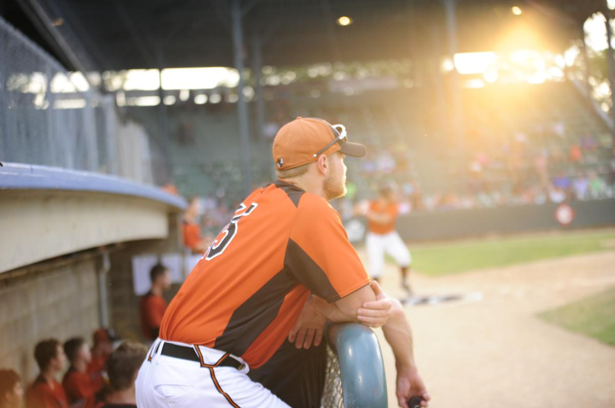 Eau Claire Express baseball player standing in the dugout at Carson Park