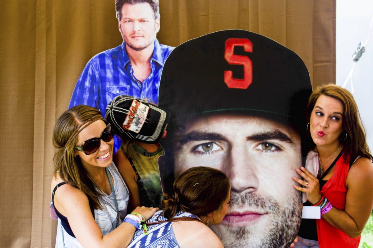 Girls posing with cardboard cutouts of Blake Shelton and Sam Hunt at Country Jam