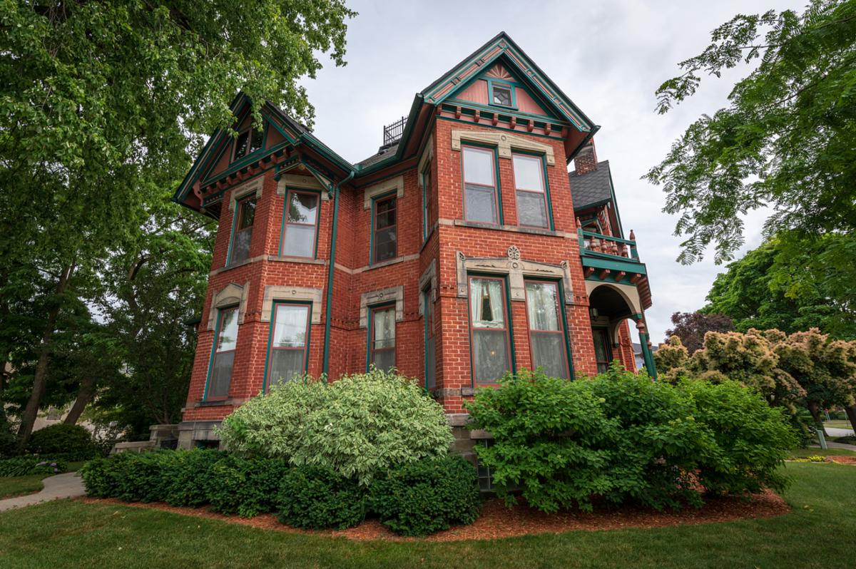 Gorgeous brick exterior of the Historic Webster House Bed & Breakfast in Bay City, surrounded by lush landscaping