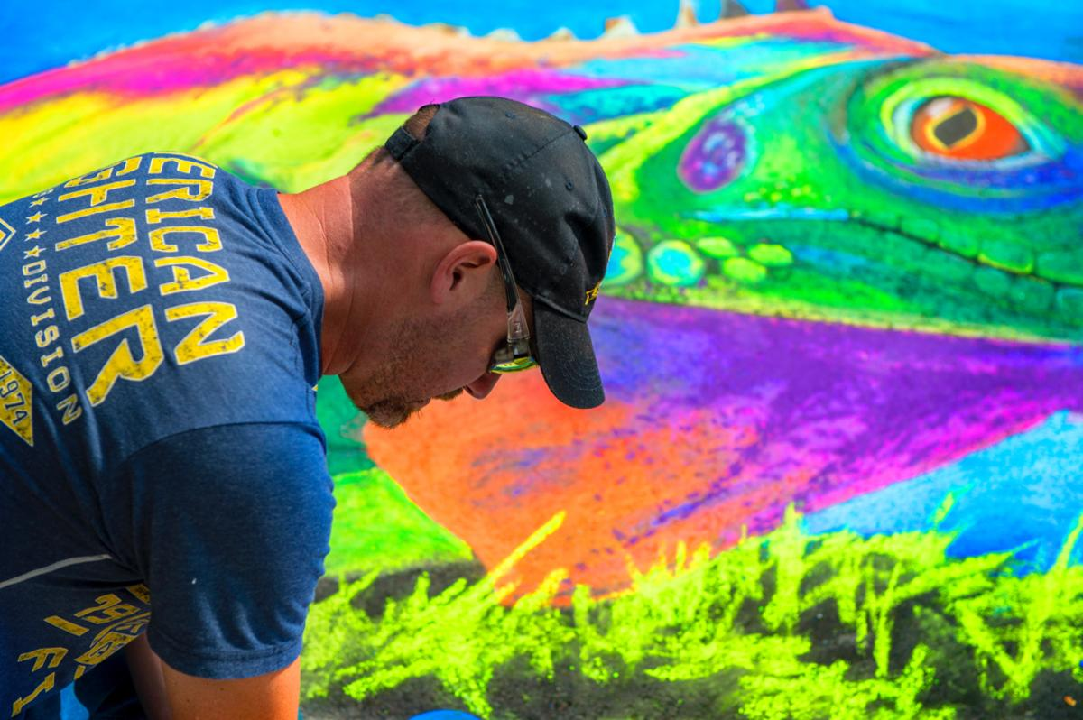 Man working on a chalk artwork of a chameleon at the Chalk Walk Art Festival in Bay City