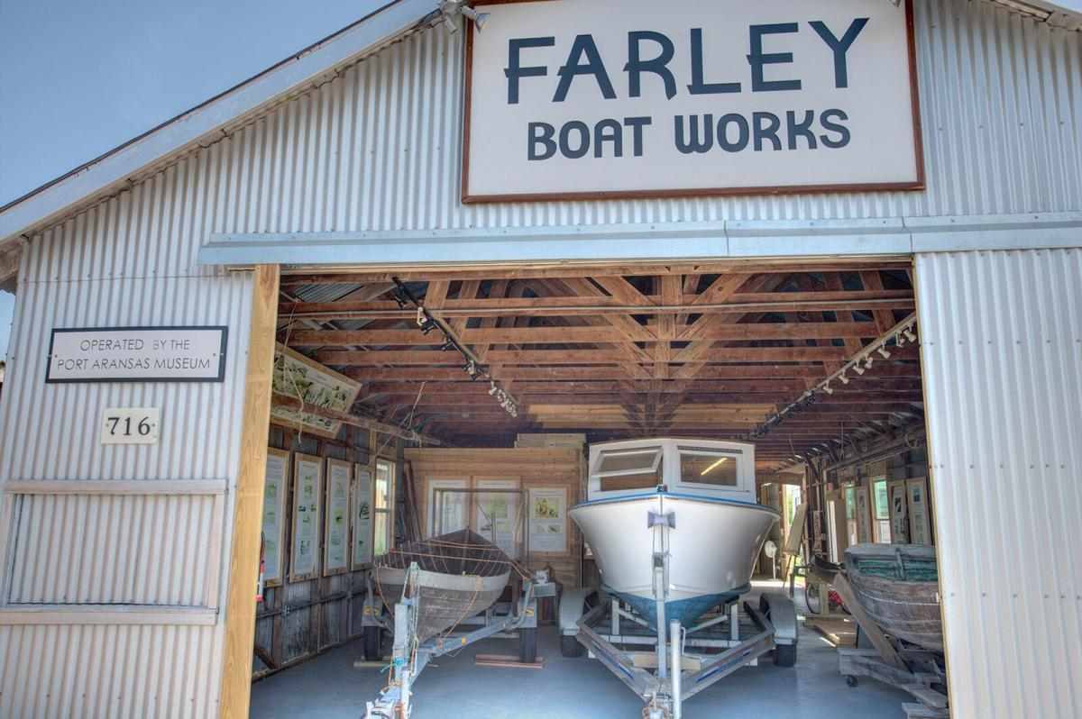 """A white boat sits on a trailer inside a building with a sign reading """"Farley Boat Works."""""""