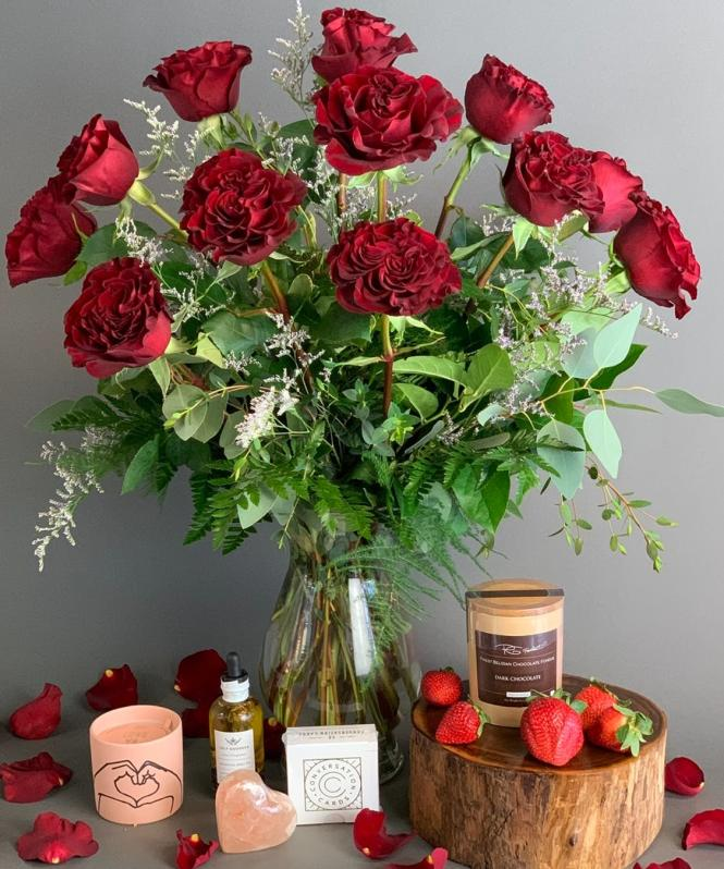 Red Roses in a vase with candle, chocolate and strawberries.